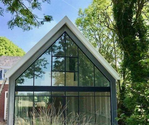 Stalen gevel met deuren bij woning in Zeeland