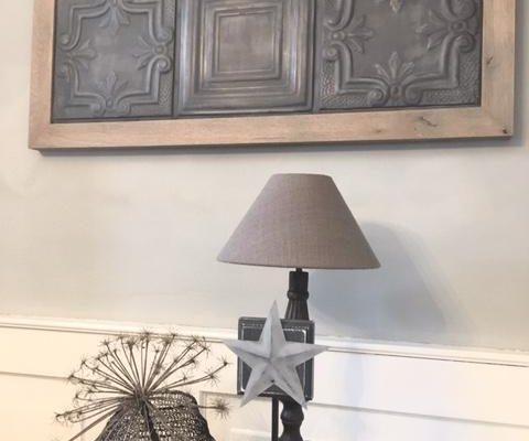 Stalen wandtegels vergrijsd met houten lijst als kunst aan de muur
