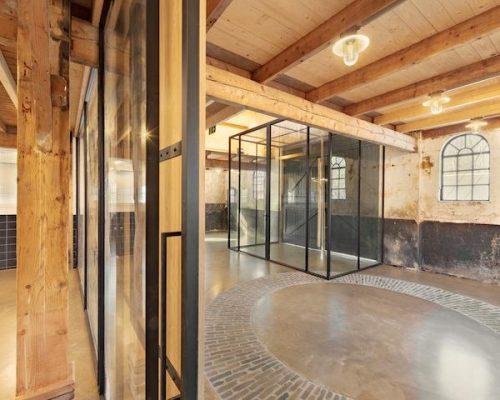 Stalen deur gecombineerd met natuurlijke materialen zoals eikenhout en natuursteen op de vloer
